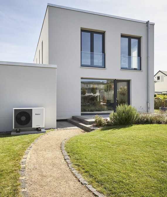 Air-to-water heat pump aroTHERM plus infront of a new building in a green garden.